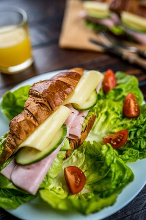 French breakfast croissant with ham, cheese and lettuce on wood table