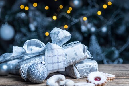Christmas gifts in silver paper and silver bulbs on wood table Imagens