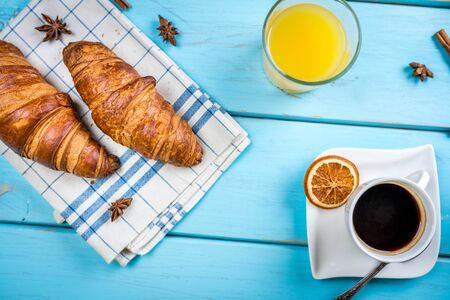 traditional french breakfast, crissant and coffee and juice on blue wood table