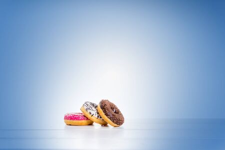 Chocolate, red, and white donuts on table and blue background
