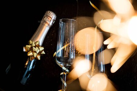 champagne glasses with golden ribbon and  sparkles on black background - new year celebration Imagens