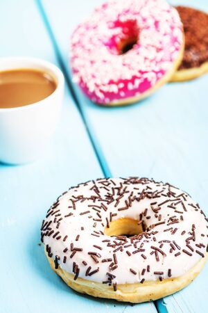 Chocolate, red, and white donuts and coffee on blue table