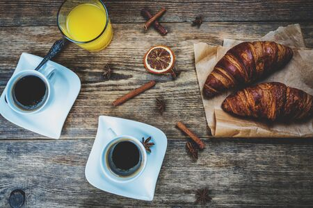 traditional french breakfast, crissant and coffee and juice on wood table