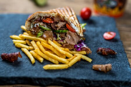 Doner kebab with vegetables and french fries on wood table Imagens