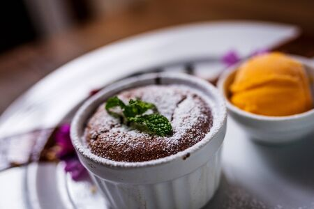 Chocolate souffle dessert and ice cream on white plate