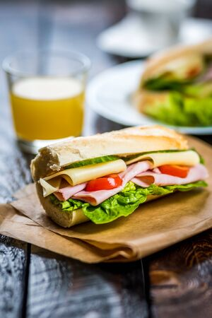 breakfast baguette with ham, cheese and lettuce on wood table