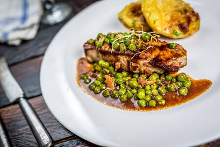 roasted veal entrecote with pea and gratin potatoes on wood table