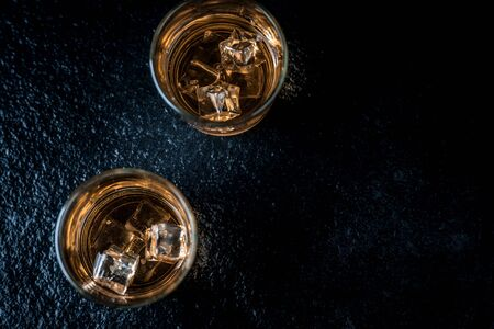 Whisky, whiskey, bourbon or cognac with ice cudes on black stone table top view