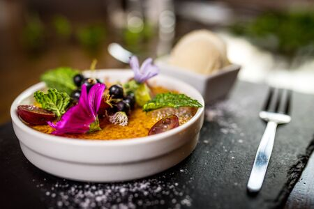 Traditional dessert Creme brulee with flowers in white bowl Фото со стока