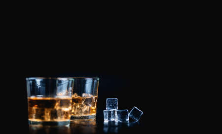 Whiskey, whiskey, bourbon or cognac with ice cudes on black stone table Archivio Fotografico