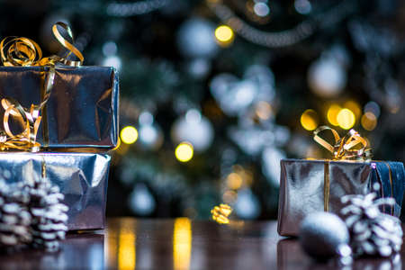 Christmas gifts in silver paper and silver bulbs on wood table Archivio Fotografico