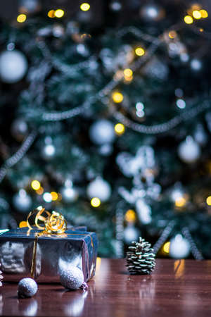 Christmas gifts in silver paper and silver bulbs on wood table Stok Fotoğraf