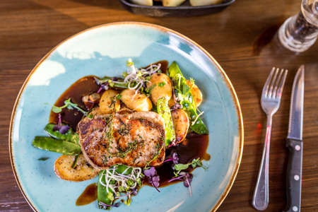 Grilled pork chop or cutlet, demi glace, gnocchi with sheep cheese on blue plate Stok Fotoğraf