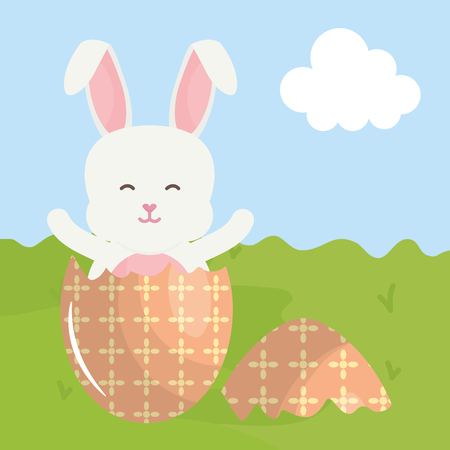 cute rabbit with broken easter egg painted in the field