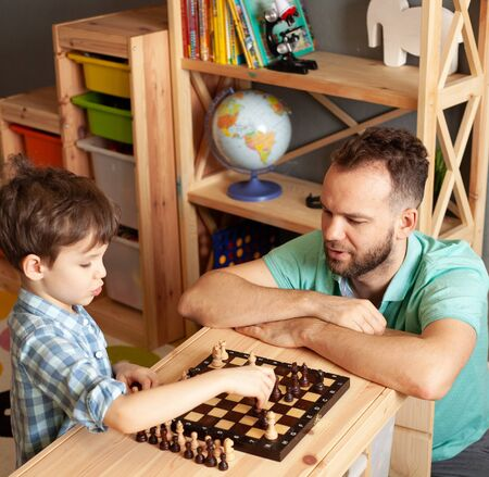 son is engaged in chess with his father, son child playing chess at home Father and son child playing chess at home, paternity leave