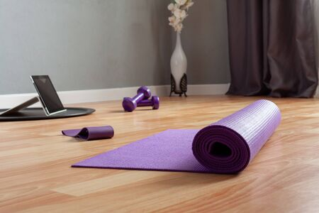 sports equipment and a tablet computer are laid out on the floor in a room. Home workouts at home using a mat, dumbbell, stretch marks. Home online fitness