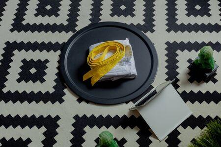 kimono uniform white yellow belt neatly folded lie on a round black tray, near the tablet computer. rug black and white geometric rug, concept of online martial arts karate, taekwondo