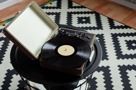 Vinyl player with plates on a black steel table. Entertainment 70s. Listen to music. Top view. Background black and white rug with geometric patterns of rhombuses Archivio Fotografico
