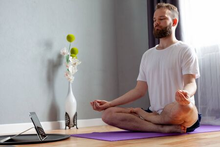 a young man is engaged in fitness at home online lessons, he is meditating, near sports equipment dumbbells, elastic bands