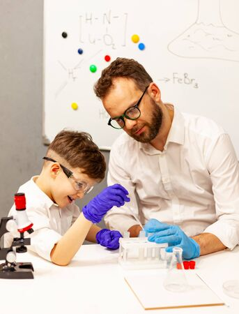 dad and son the child stayed at home conduct experiments on a white table, behind them on the wall is a white Board magnetic-marker, classes with a child at home, educational classes at home for children, entertainment with children in self-isolation 版權商用圖片