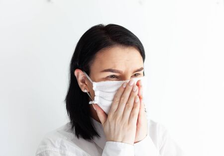 woman in medical mask on a white background, virus protection, doctor girl brunette in white clothes