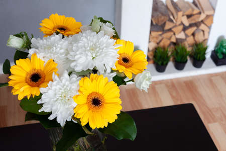 bouquet of chrysanthemums on a dark table near a white fireplace Imagens