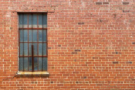 a red brick wall with a rusted old window and bars Banque d'images
