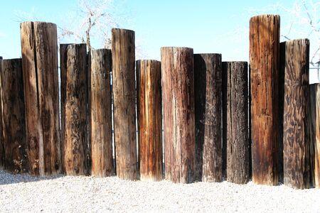 una línea de postes de cerca de madera junto al mar