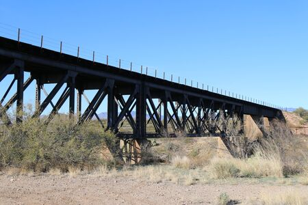 a railroad bridge in the desert with river crossing below Stock Photo