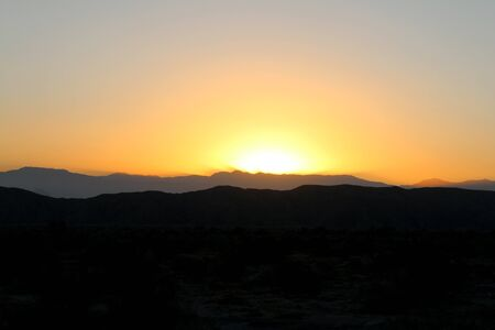 a desert mountain view with bright yellow and orange sunset in silhouette
