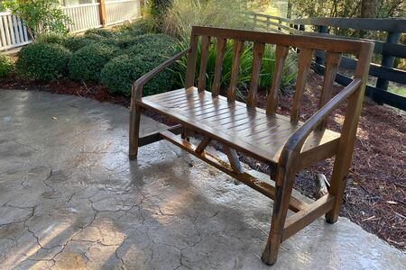 a stylish shiny wooden park garden bench on a stone path or porch in the sunlight with shadows