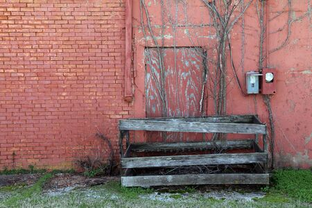 a red brick warehouse with  back shipping doors boarded up and unused with grass