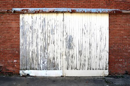 bright white painted yet peeling warehouse shipping double doors on red brick building