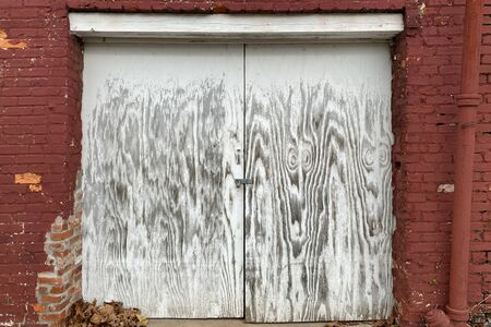 a pair of faded white painted locked shipping and receiving dock doors on a back alley red brick warehouse