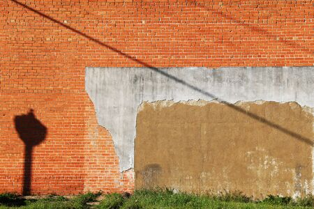 an exterior red and orange brick wall with grass verge on a bright sunny afternoon with lamp post casting shadows