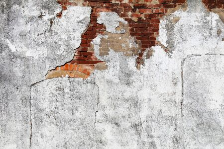 a faded white concrete wall with exposed red brick details with bright sunlight shadows Stock Photo