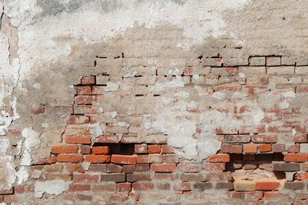a beautiful old decaying concrete and red brick exterior wall exposed and falling apart