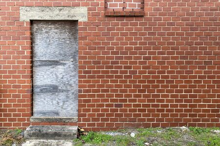 a boarded up door way on an abandoned red brick back alley warehouse building Stock Photo