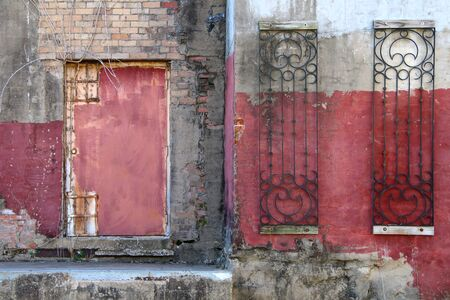 a red fadeing painted dirty warehouse in an alley with red door rusted and concrete steps Stock Photo