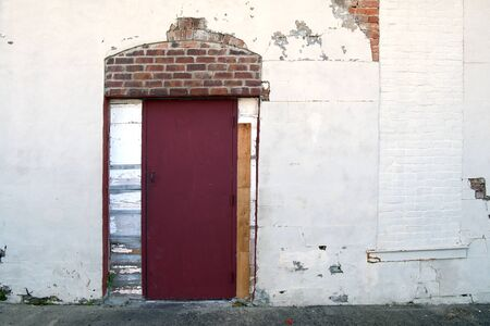 a white stucco wall at an alley building with a red door with exposed brick