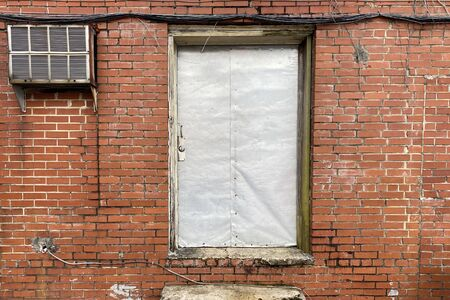 an old locked sheet metal back door on a retro red brick warehouse building
