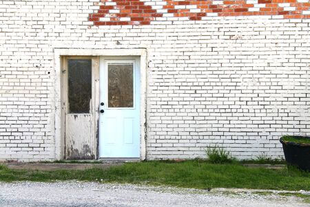 an abandoned painted white brick store doorway with exposed red brick