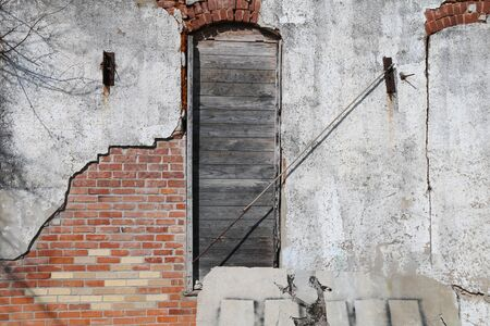 a boarded up arched window on a faded stucco red brick wall building Stock Photo