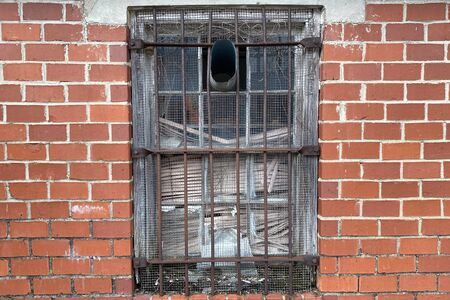 a rusty old steel rod window on a vintage red brick building wall