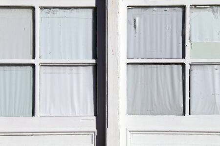 a pair of old vintage pane glass windows on a white building