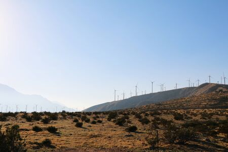 a sunset contrast with desert mountains ridge and distance wind turbines Stock Photo