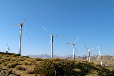 a beautiful desert mountain crest with a row of wind farm turbines