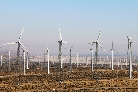 a very large desert distant wind farm with rare retro turbines