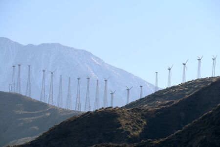 a mountain valley and crest with a large vintage wind turbine farm in the distance
