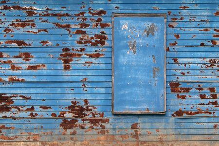 a blue rusty barn farm building wall with boarded up window Stock Photo